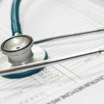 Stetoskop leżący na dokumentach zapytania ofertowego centrum medycznego Ars Medica
