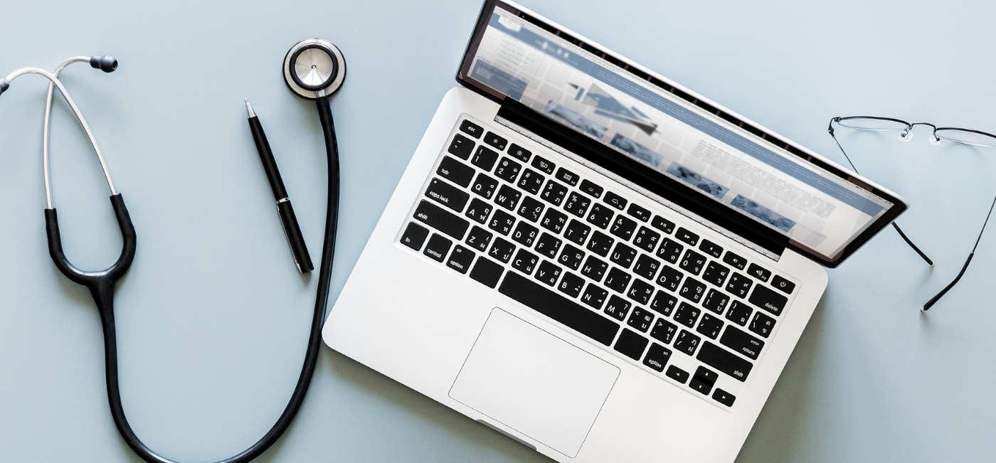 Laptop leżący na biurku obok stetoskopu